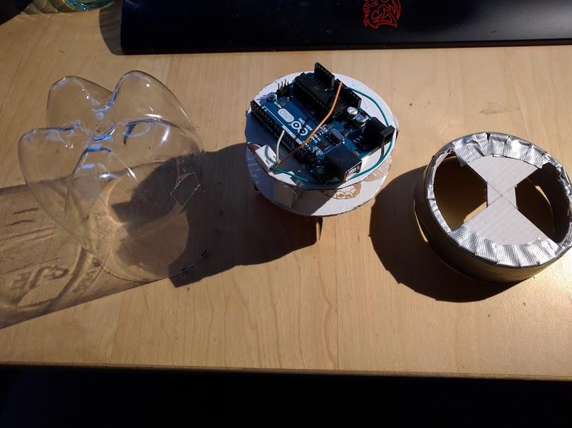 Deksel fra en Olden 1,5 liters flaske, plate som holder Arduino, servo og vinger, bunnlokk med åpninger til matutslipp.